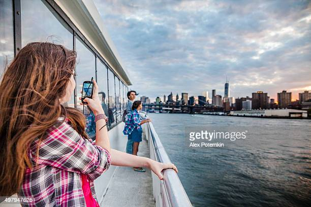 Teenager girl recording video with smart phone at ferry