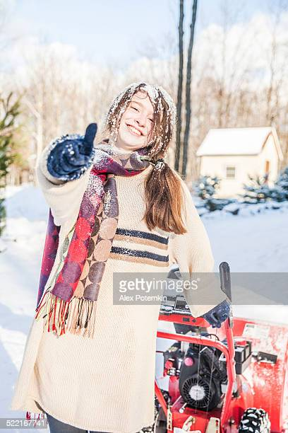 Teenager girl remove the snow with snowmashine
