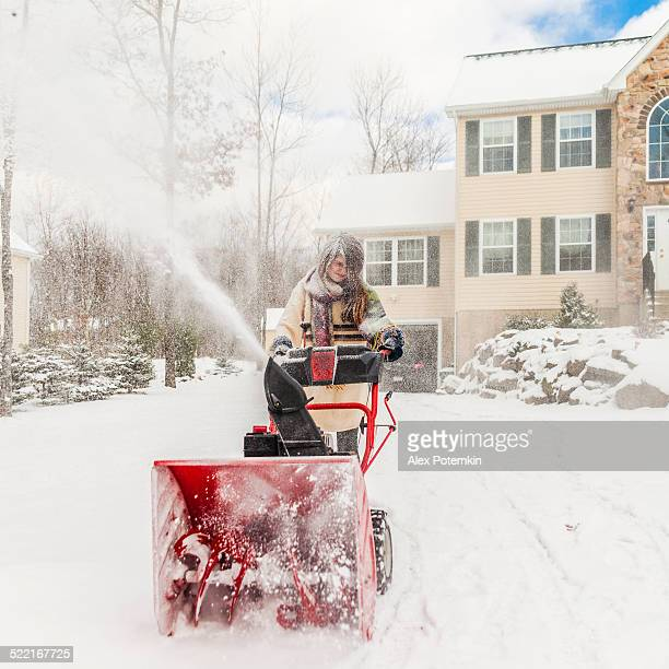 Teenager girl remove the snow with snowplow