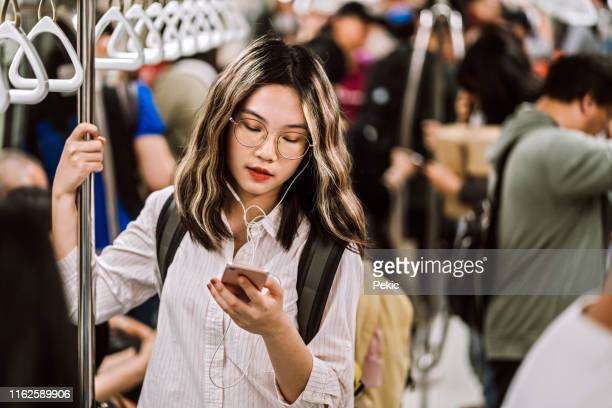 地下鉄の電車に乗って、携帯電話を使用してティーンエイジャーの女の子 - 内部 ストックフォトと画像