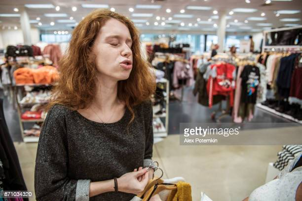teenager girl shopping in the clothing store during the holiday's sale - alex potemkin or krakozawr stock pictures, royalty-free photos & images