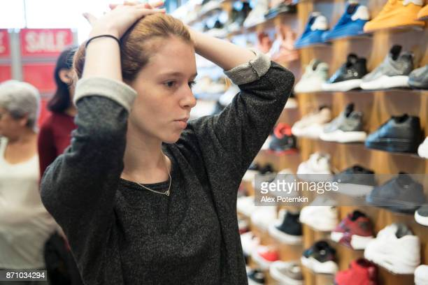 Teenager girl shopping sneackers in the shouse store during the holiday's sale