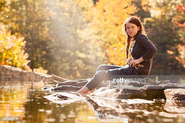 吸うティーンエイジャーの女の子に位置し、川ロック