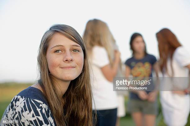 Teenager girl sitting in front of socializing friends