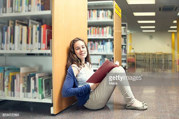 Teenager girl sitting on floor at a library.