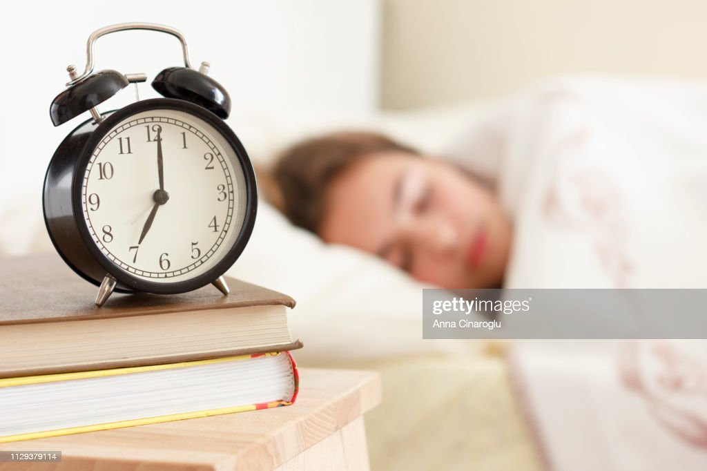 Teenager girl sleeping in a white bed. Alarm clock in the foreground on a pile of books : Stock Photo