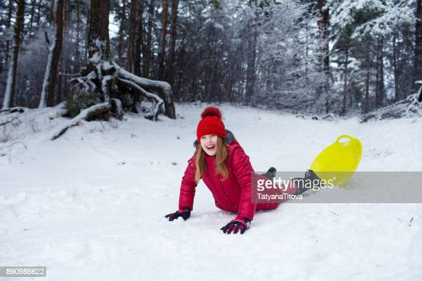 teenager girl sliding with bob and falling in the snow. - latvia stock pictures, royalty-free photos & images