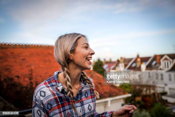 Teenager girl standing in the balcony with houses in the background