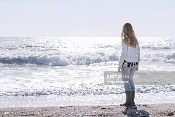 Teenager girl standing on shore looking at the sea