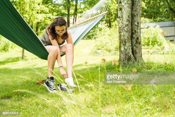 teenager girl taking on shoes before leaving the hammock - one teenage girl only stock pictures, royalty-free photos & images