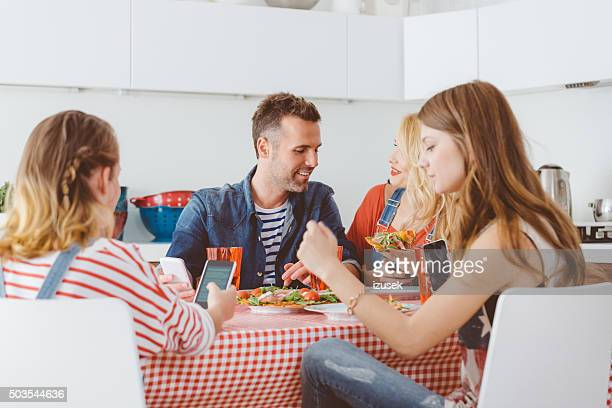 Teenager girl using smart phone during lunch with family