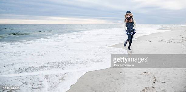 Teenager girl walking along the ocean at the Jones Beach