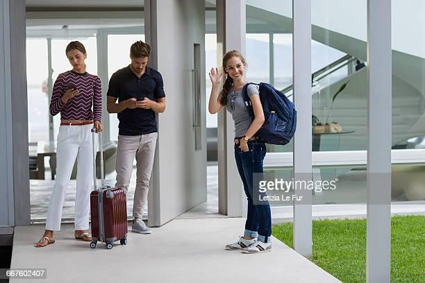 Teenager girl waving hand with her guests standing on doorway