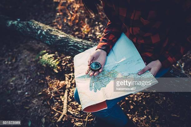 Adolescent fille avec Boussole lire une carte dans la forêt.