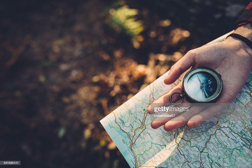 Chica adolescente con brújula leer un mapa en el bosque : Foto de stock