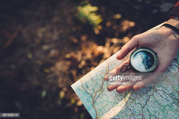 teenager girl with compass reading a map in the forest - cartography stock photos and pictures