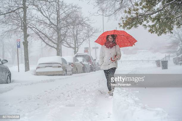 Teenager girl with umbrella under snowfall at the street