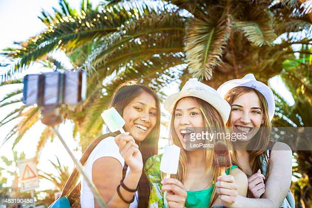 Teenager girls eating an ice cream and taking a selfie