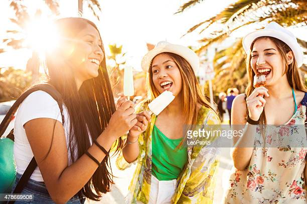 Teenager girls eating an ice cream in summer