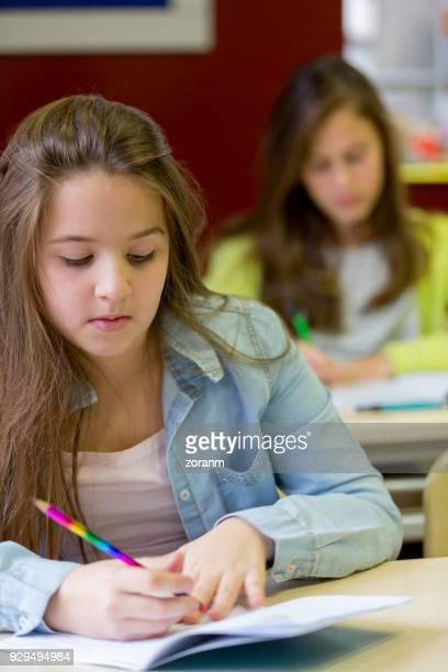 teenager girls in classroom writing - high school musical: the musical: the series stock photos and pictures