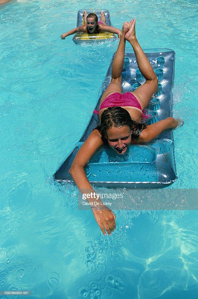 Teenager Girls On Pool Raft In Swimming Pool Stock Photo
