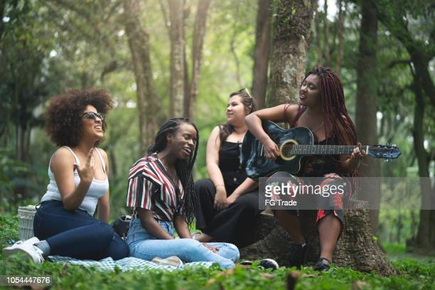 teenager girls playing guitar and singing at park - the weekend singer stock pictures, royalty-free photos & images