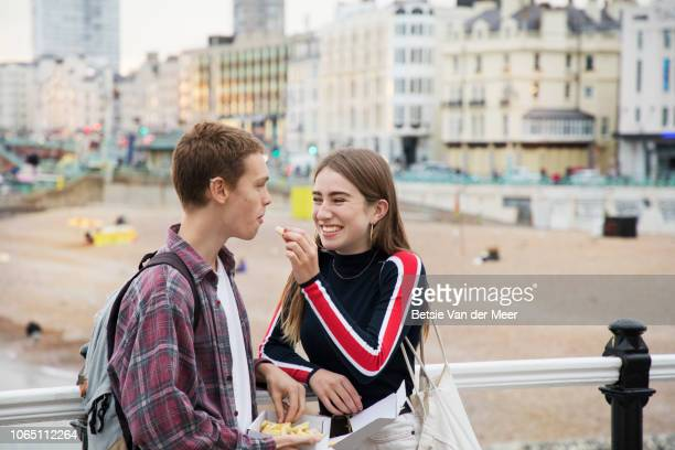 teenager gives chip to boyfriend standing on promenade. - boyfriend stock pictures, royalty-free photos & images
