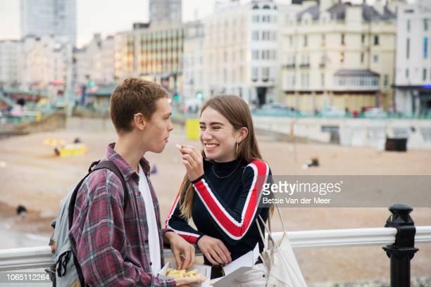 teenager gives chip to boyfriend standing on promenade. - vriendje stockfoto's en -beelden