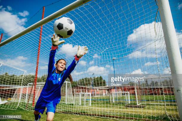 teenager goalkeeper playing soccer and defending penalty kicks - portiere posizione sportiva foto e immagini stock