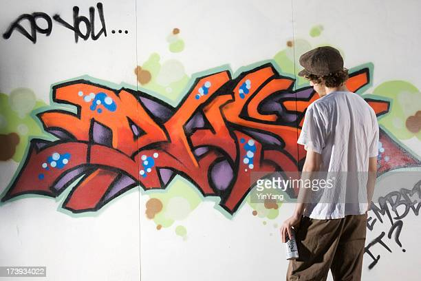 Teenager Graffiti Artist Spray Painting Wall Street Art, Rebelling, Vandalizing