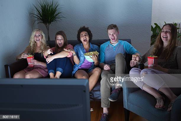 teenager group of friends watching humorous movie, tv show together - kanaal stockfoto's en -beelden