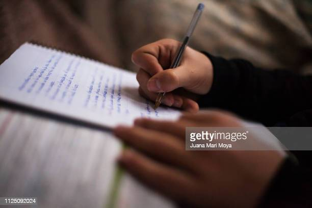 teenager hands writing in a notebook.  he is doing the tasks of the institute.  spain - handwriting stock pictures, royalty-free photos & images