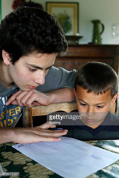 Teenager helping his brother with his homework