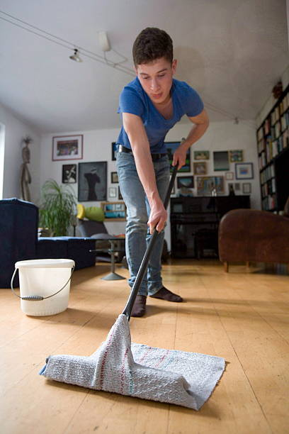 Teenager helps in household and cleans the floor, on October 03, 2014 in Bonn, Germany.