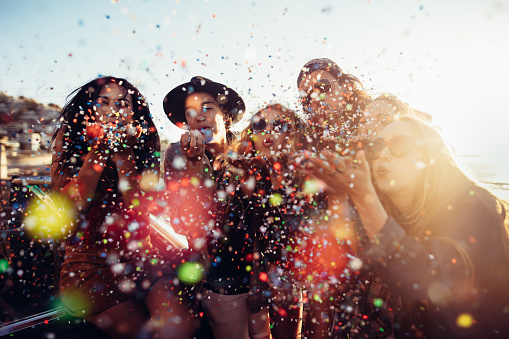 Teenager hipster friends celebrating by blowing colorful confetti from hands - gettyimageskorea