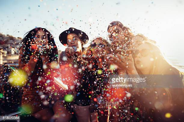 Teenager hipster friends celebrating by blowing colorful confetti from hands