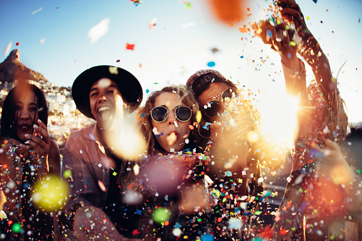 Teenager hipster friends partying by blowing colorful confetti from hands 513550806