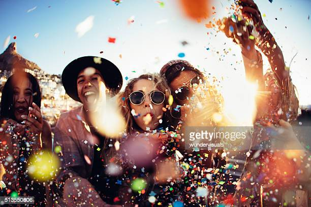 teenager hipster friends partying by blowing colorful confetti from hands - bontgekleurd stockfoto's en -beelden