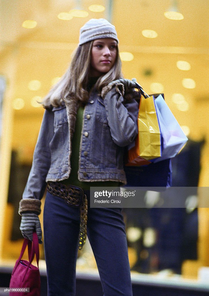 Teenager holding shopping bags, standing in front of store window. : Stockfoto