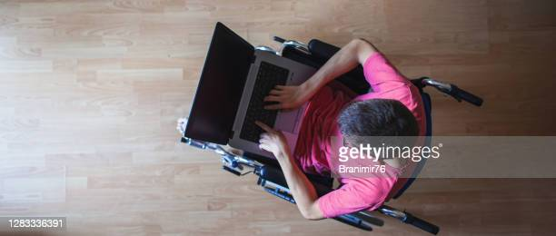 a teenager in a wheelchair works on a laptop and communicates with friends - computer equipment stock pictures, royalty-free photos & images