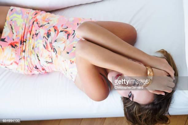 Teenager in mini dress lying on sofa