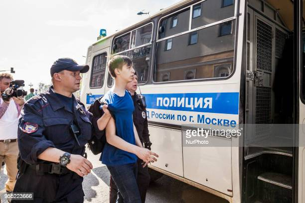 Teenager is arrested by riot police in a demonstration against Putin in Pushkin square Moscow Russia on 5 May 2018