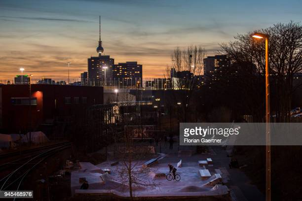 A teenager is cycling on a skating rink at dusk in Berlin In the background the TV tower on April 06 2018 in Berlin Germany