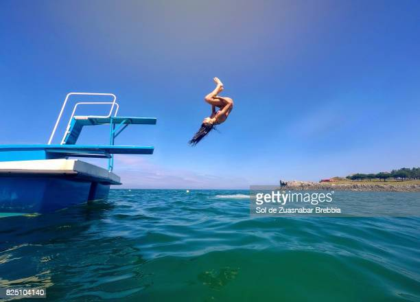 teenager jumping giving tumbling from a trampoline on the sea - diving board stock pictures, royalty-free photos & images