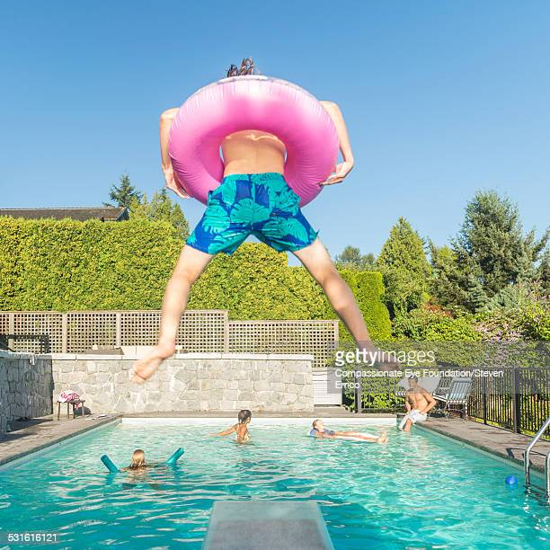 Teenager jumping into pool with rubber ring