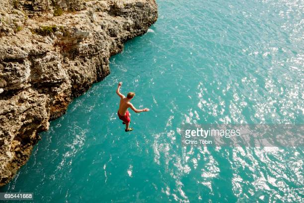 teenager jumping off cliff into shimmering blue water - majorca stock pictures, royalty-free photos & images