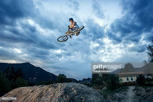 Teenager jumping on BMX bike under dramatic sky.