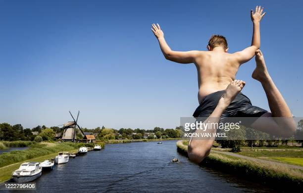 A teenager jumps into the water from a bridge at Oudorp some 50kms north of Amsterdam on June 25 2020 as the summer heat starts to build across...