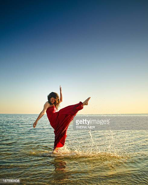 teenager kicking high with her foot in the beach - long dress stock pictures, royalty-free photos & images