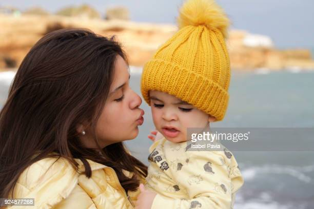 Teenager kissing baby boy